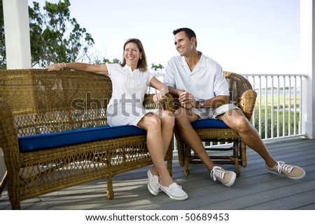 Happy mid-adult couple sitting together on terrace on vacation - stock photo