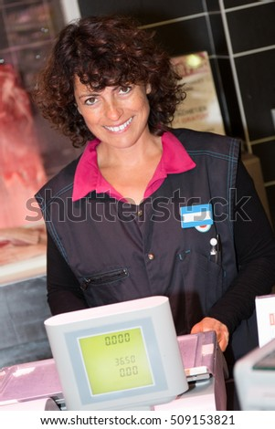Happy mid adult female butcher standing in front of cash register