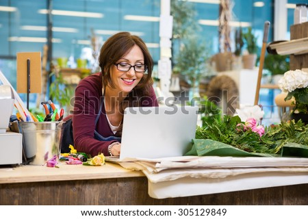 Happy mid adult female florist using laptop at counter in flower shop - stock photo