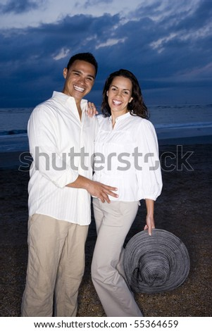 Happy mid-adult Hispanic couple smiling on beach at dawn - stock photo