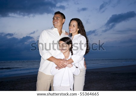 Happy mid-adult Hispanic family with 9 year old girl smiling on beach at dawn - stock photo