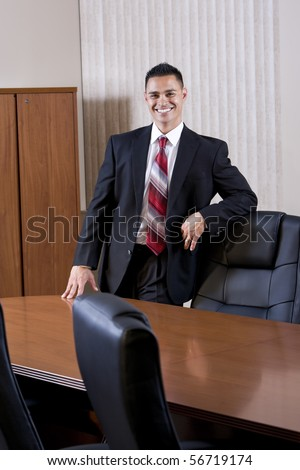 Happy mid-adult Hispanic office worker in business suit standing in boardroom - stock photo