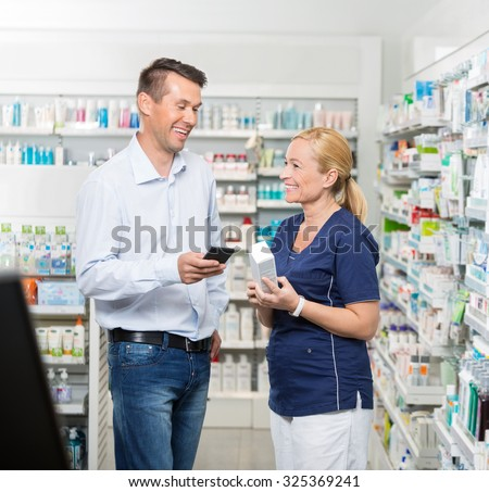 Happy mid adult male customer holding mobile phone while pharmacist showing product in pharmacy - stock photo