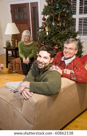 Happy mid-adult man and senior parents by Christmas tree - stock photo