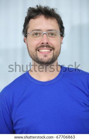 happy mid adult man with glasses and beard smiling - stock photo