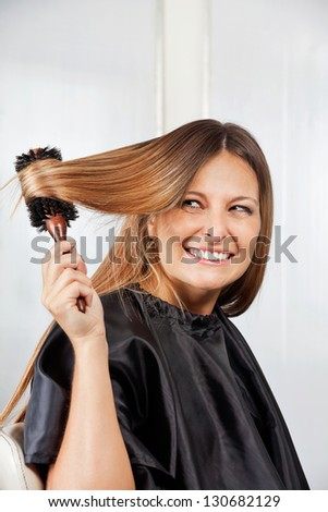 Happy mid adult woman brushing hair in salon - stock photo