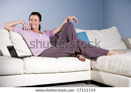 Happy mid-adult woman sitting on couch smiling with laptop - stock photo