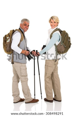 happy mid age  couple with backpacks looking back - stock photo
