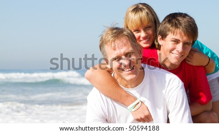 happy mid-aged father and children on beach - stock photo