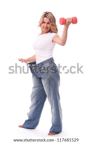 Happy mid aged woman in big pants after weight losing with dumbbell in hand - stock photo