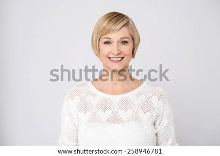 Happy mid woman posing over grey - stock photo