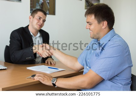 Happy Middle Age Businessmen Showing Handshake Gesture at Desk Area After Discussing Business Deals - stock photo