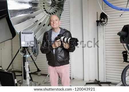 Happy middle age photographer with camera and equipments in studio - stock photo