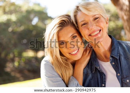 happy middle aged blond mother and adult daughter outdoors - stock photo
