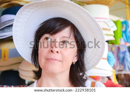 Happy middle aged brunette with hat in store