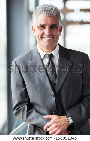 happy middle aged businessman looking at the camera - stock photo