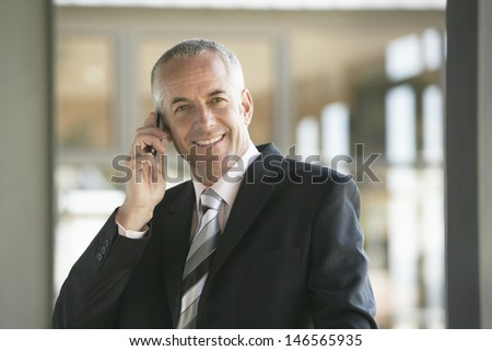 Happy middle aged businessman using mobile phone in office - stock photo