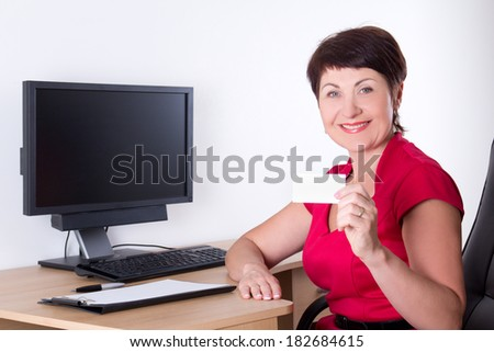 happy middle aged businesswoman with visiting card sitting in office - stock photo