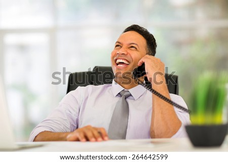 happy middle aged corporate worker talking on landline phone in office - stock photo