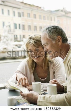 Happy middle aged couple at outdoor cafe reading map in Rome - stock photo