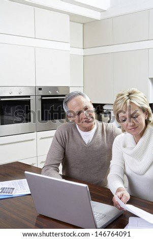 Happy middle aged couple calculating home finances on laptop at kitchen table - stock photo