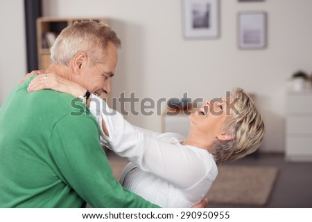 Happy Middle Aged Couple Dancing at the Living Room While Holding Each Other and Laughing. - stock photo