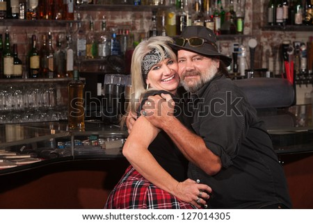 Happy middle aged couple embracing in a tavern - stock photo