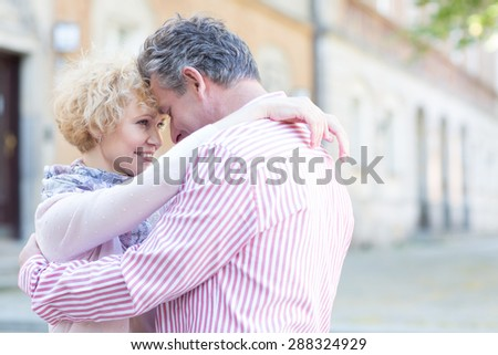 Happy middle-aged couple embracing in city - stock photo