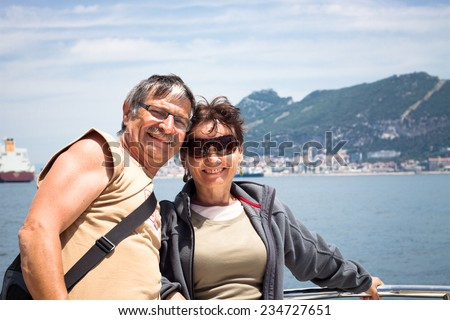 Happy middle aged couple enjoying summer boat trip. - stock photo