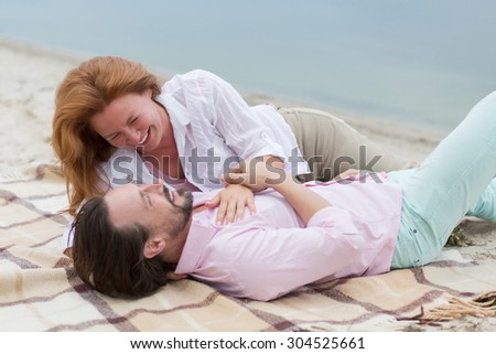 Happy middle-aged couple enjoying their summer holiday together near by sea. People smiling and looking at each other. - stock photo