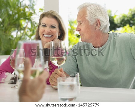 Happy middle aged couple having wine with friend at verandah table - stock photo