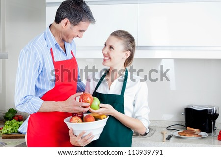 Happy middle aged couple in kitchen preparing food - stock photo