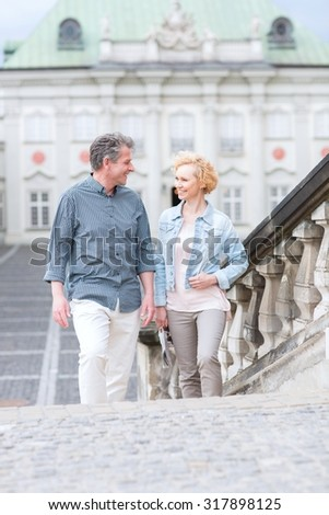 Happy middle-aged couple looking at each other while climbing steps - stock photo