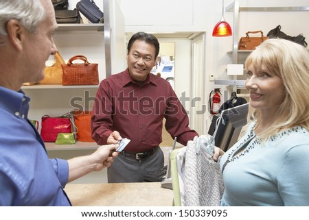 Happy middle aged couple paying for clothes through credit card at counter in store - stock photo