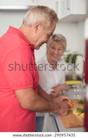 Happy Middle Aged Couple Preparing Something Homemade Fresh Food for Dinner at the Kitchen - stock photo