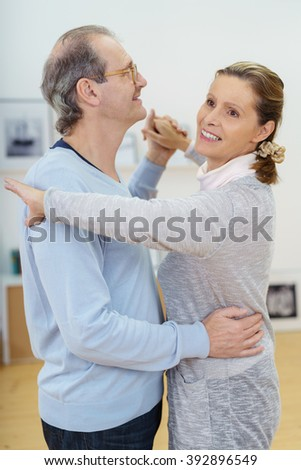 Happy middle-aged couple relaxing dancing together at home in the living room with smiles of enjoyment