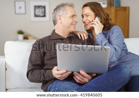Happy middle aged couple seated on white couch in their living room with laptop while the wife makes a phone call - stock photo