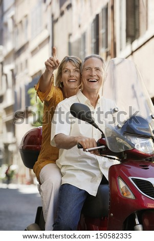 Happy middle aged couple sightseeing on scooter in Rome; Italy - stock photo