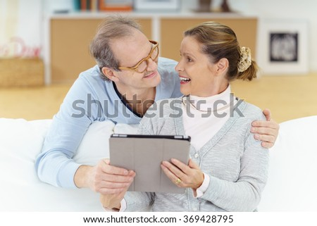happy middle-aged couple sitting on the sofa holding a tablet-pc and looking at each other with a smile