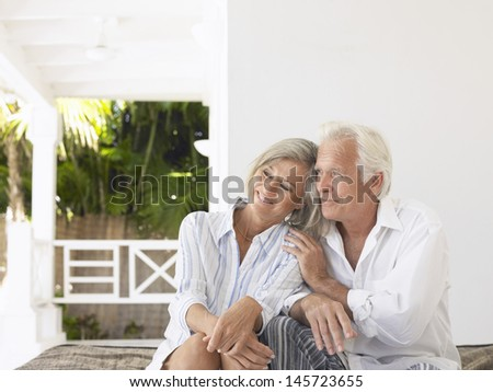 Happy middle aged couple sitting on verandah - stock photo