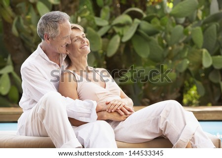 Happy middle aged couple spending romantic time by pool - stock photo