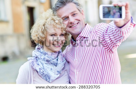 Happy middle-aged couple taking selfie through smart phone outdoors - stock photo