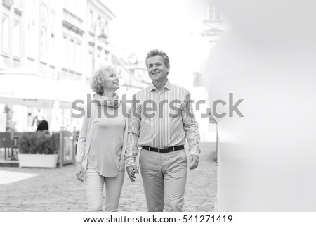 Happy middle-aged couple talking while walking in city