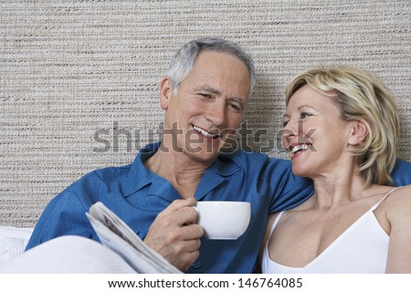 Happy middle aged couple with coffee cup reading newspaper in bed - stock photo