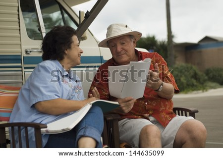Happy middle aged couple with magazines relaxing outside their motor home - stock photo