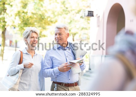 Happy middle-aged couple with map walking in city - stock photo
