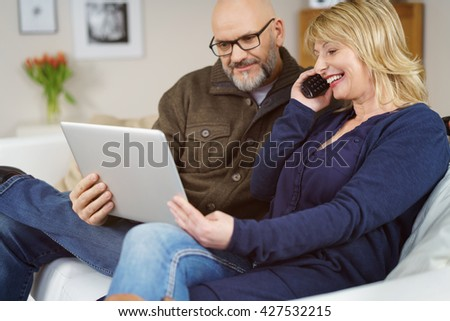 Happy middle aged European couple on phone with technical support as they smile and look at their open laptop computer - stock photo