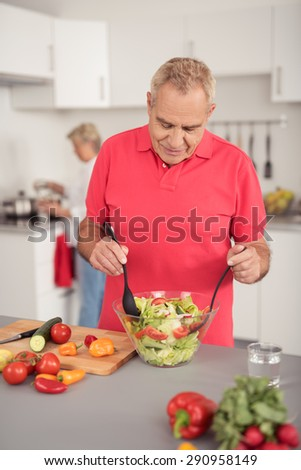 Happy Middle Aged Husband Preparing Fresh Healthy Vegetable Salad at the Kitchen with his Wife. - stock photo