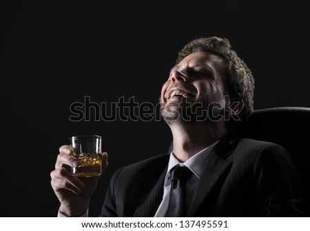 Happy middle aged man drinking whiskey against black background - stock photo