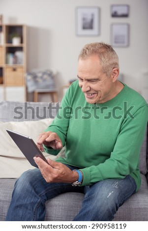 Happy Middle Aged Man in Casual Wear, Sitting at the Couch in the Living Room While Using his Tablet Computer. - stock photo